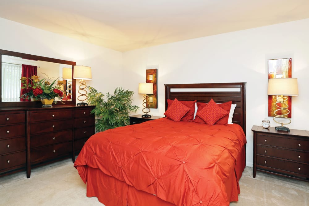 Spacious bedroom featuring large dresser with mirror red comforter on king-size bed in an apartment at Blackhawk Apartments in Elgin, Illinois