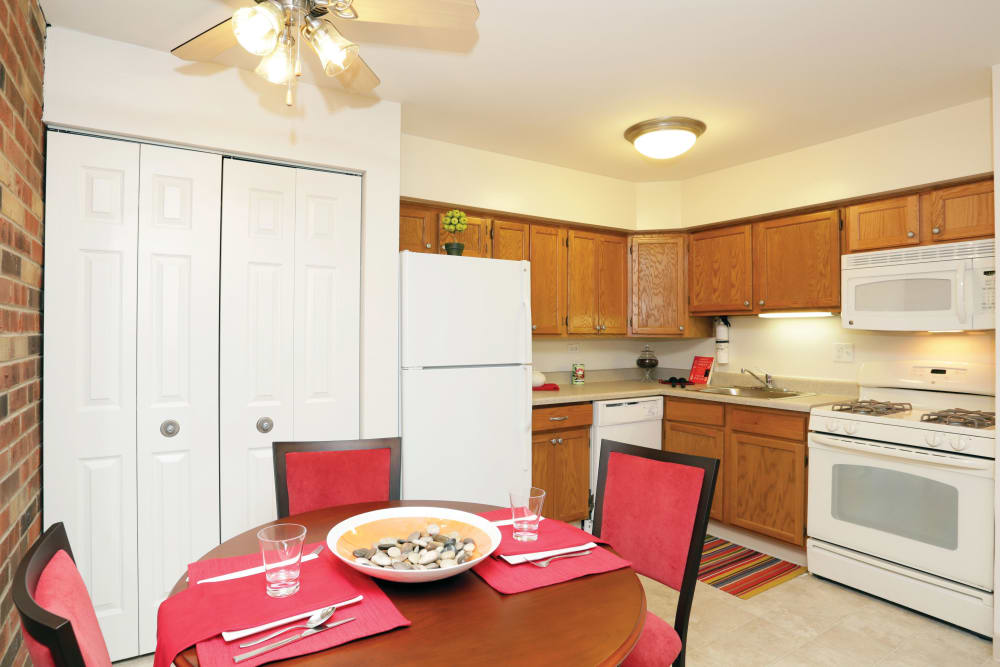 A modern kitchen featuring white appliances and brightly colored red chairs and table at Blackhawk Apartments in Elgin, Illinois