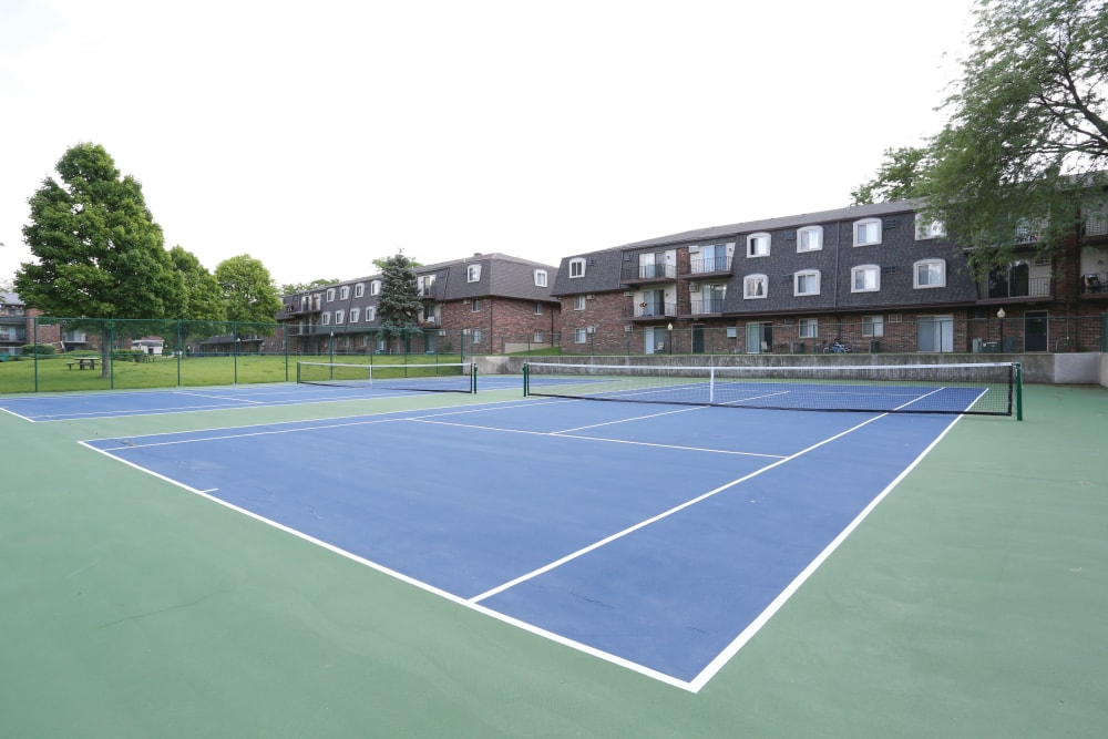 Tennis courts with apartments in the background at Blackhawk Apartments in Elgin, Illinois