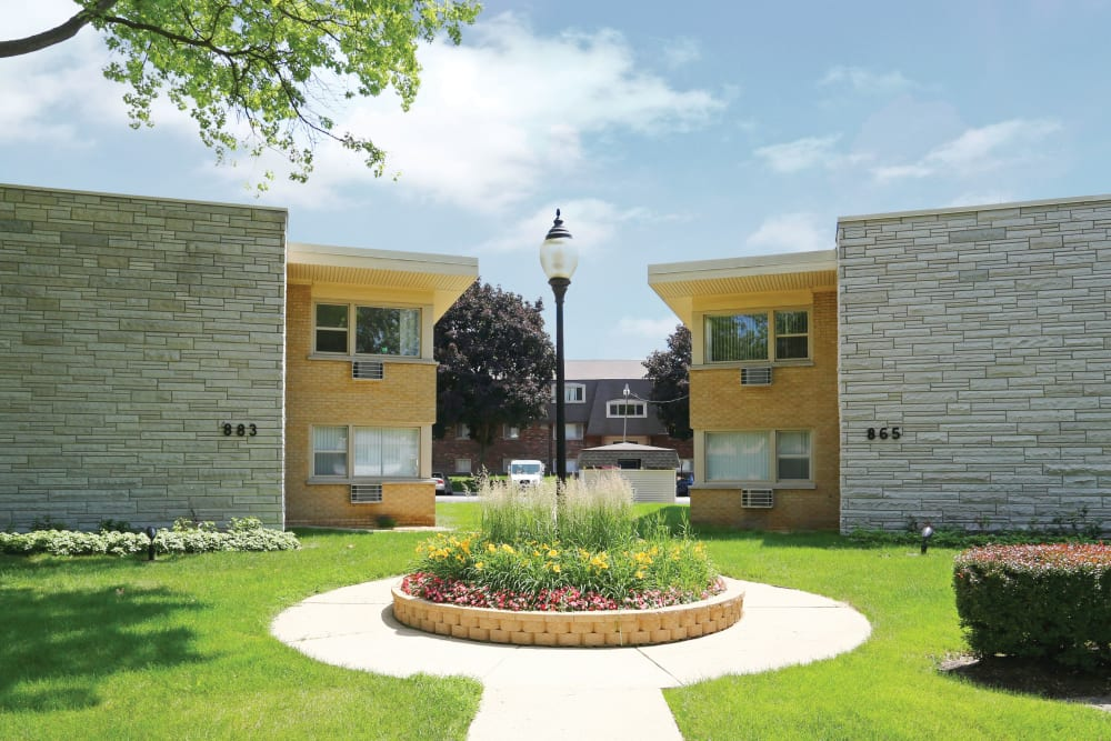 A walkway path with beautiful landscaping and apartment buildings in the background at Blackhawk Apartments in Elgin, Illinois