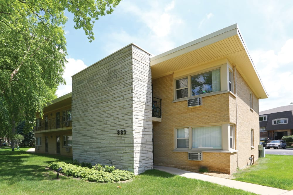 Exterior of building with mature trees and pathway at Blackhawk Apartments in Elgin, Illinois