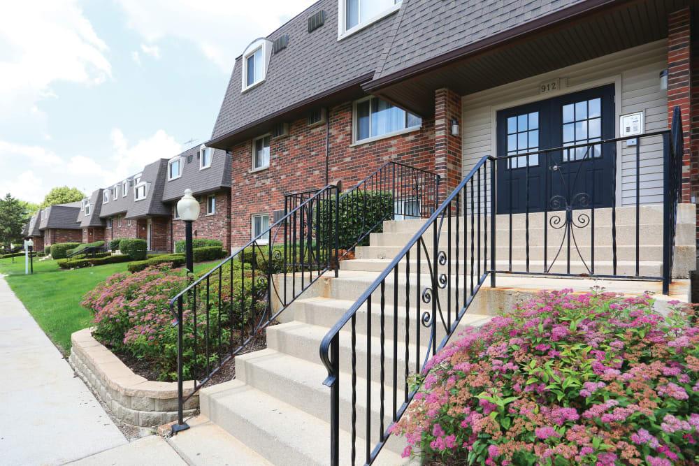 Staircase leading past flowers to entrance of building at Blackhawk Apartments in Elgin, Illinois