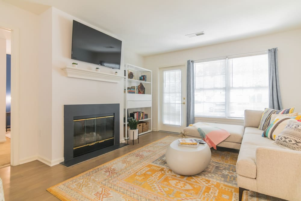Featuring large windows for ample natural light and a fireplace this is a stylish living room at Eagle Rock Apartments at Freehold in Freehold, New Jersey
