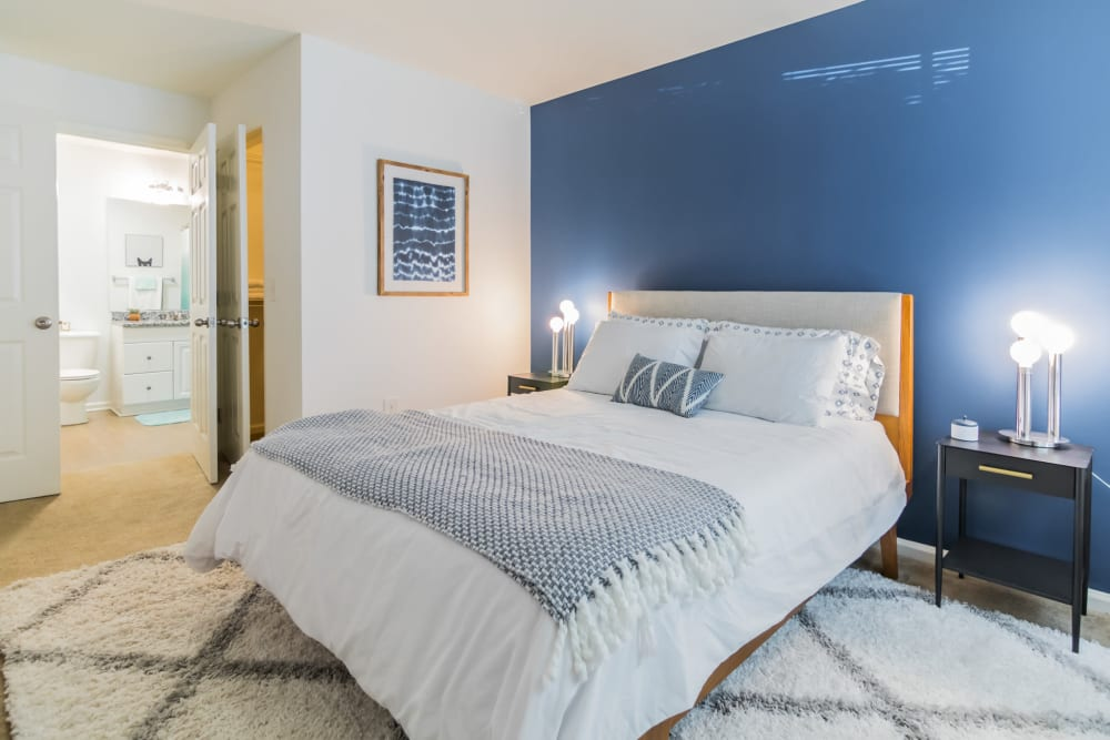 Spacious bedroom featuring accent wall painted blue and comfortable bed in an apartment at Eagle Rock Apartments at Freehold in Freehold, New Jersey
