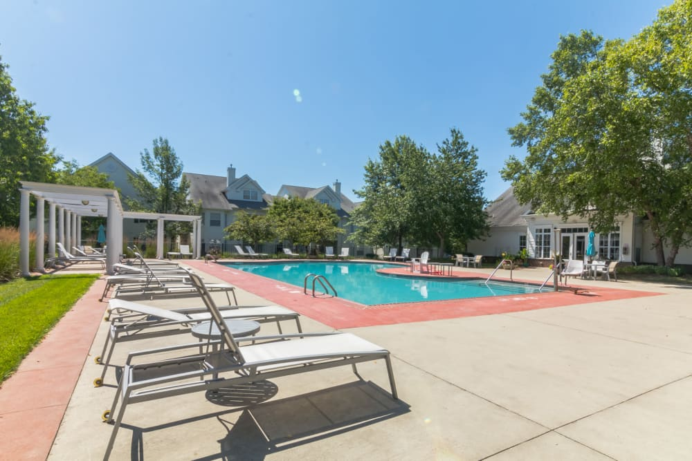 Outdoor community pool with lounge chairs and mature trees in the background at Eagle Rock Apartments at Freehold in Freehold, New Jersey