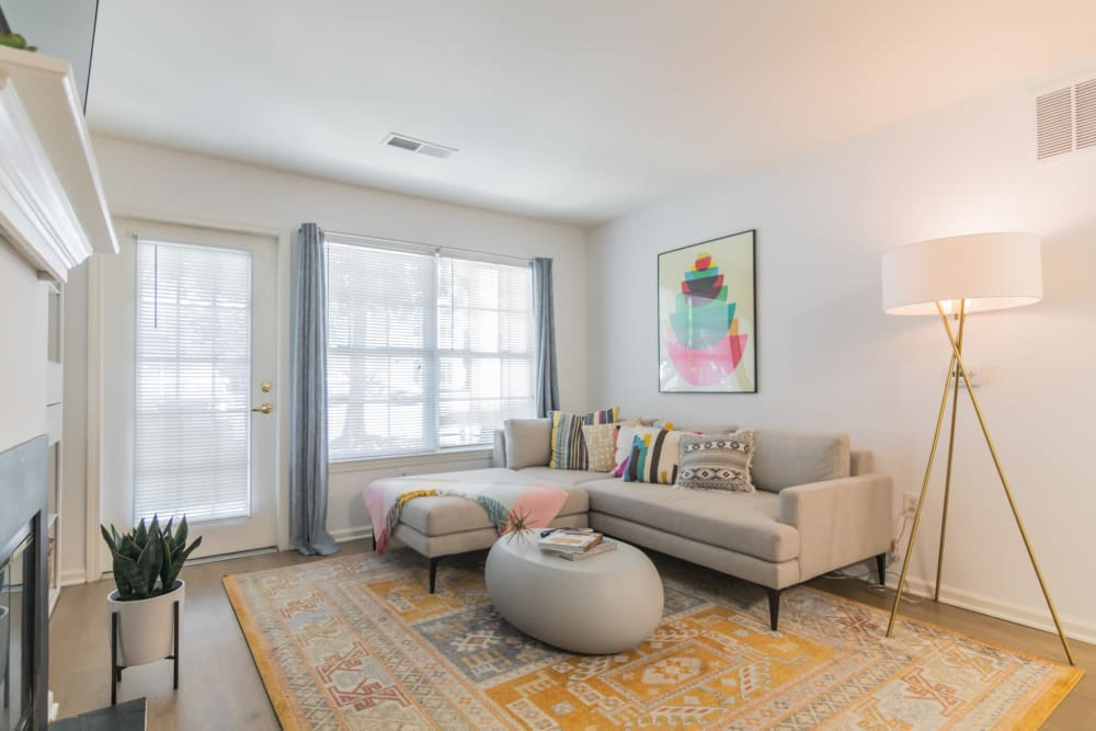 Stylish living room interior featuring area rug couch seating and large windows for ample natural light at Eagle Rock Apartments at Freehold in Freehold, New Jersey