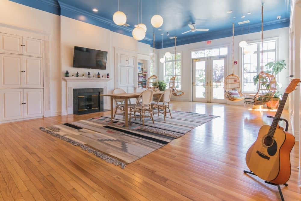Spacious clubhouse interior with hardwood floors guitar in the foreground fireplace and seating area in the background at Eagle Rock Apartments at Freehold in Freehold, New Jersey