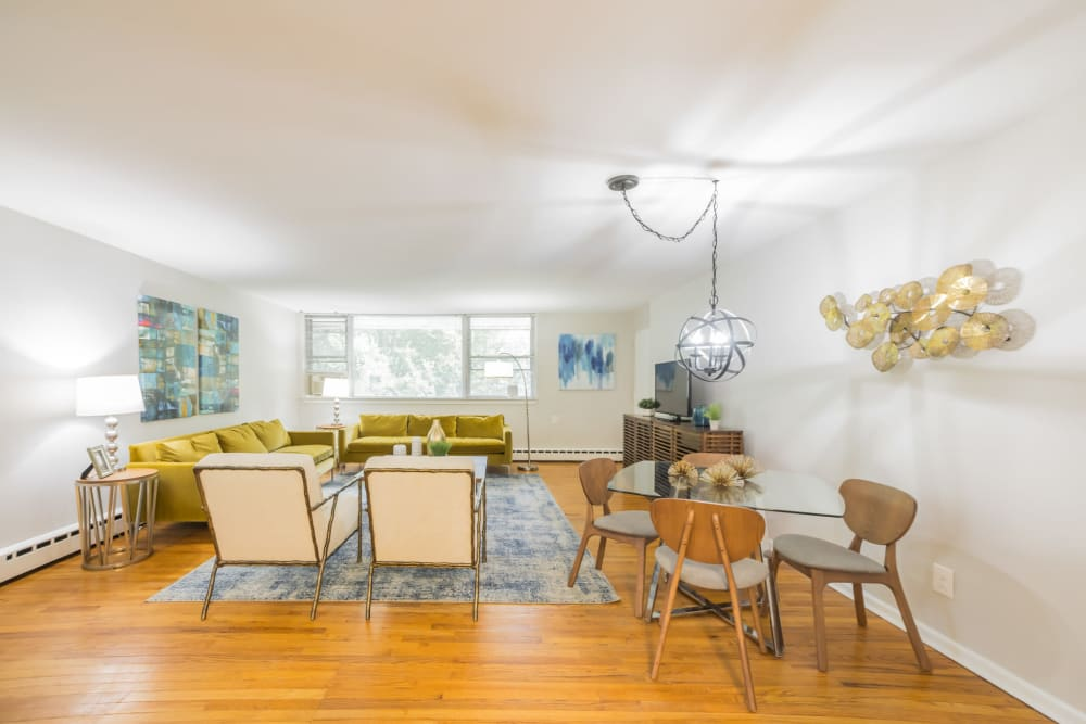 Living room and dining area with hardwood floors and lots of natural light from windows in an apartment at Cherokee Apartments in Philadelphia, Pennsylvania