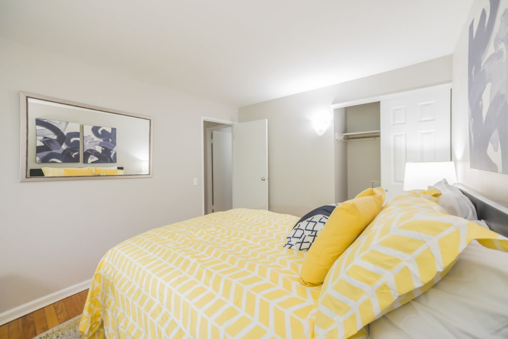 Well that bedroom features queen size bed with yellow comforter and art on the walls in an apartment at Cherokee Apartments in Philadelphia, Pennsylvania