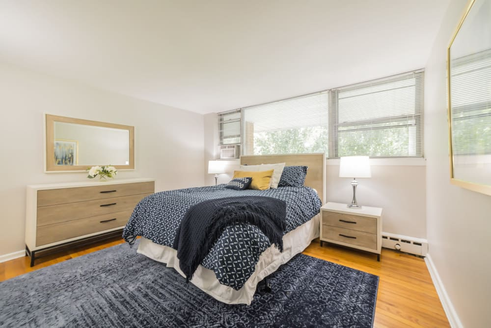 A Spacious bedroom with lots of natural light from large windows pictures comfortable bed and dresser with large vanity mirror in an apartment at Cherokee Apartments in Philadelphia, Pennsylvania