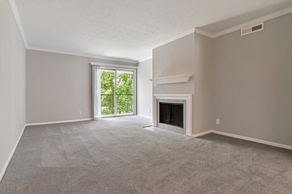Spacious living room featuring a fireplace and wall-to-wall carpeting in an apartment at Crest at Riverside in Roswell, Georgia