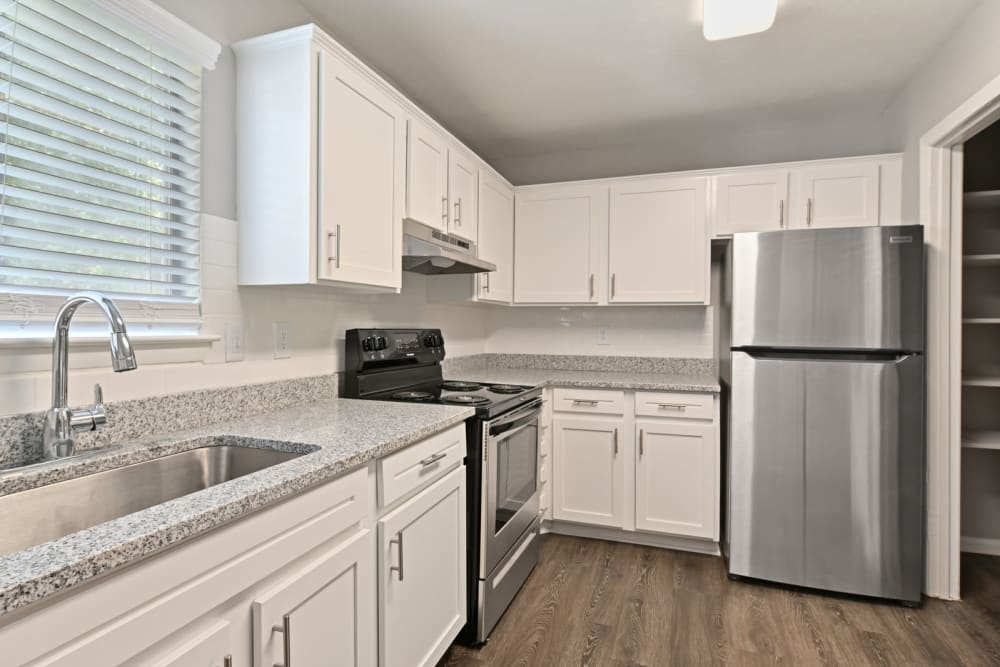 Modern kitchen with white cabinets and stainless steel appliances in an apartment at Crest at Riverside in Roswell, Georgia