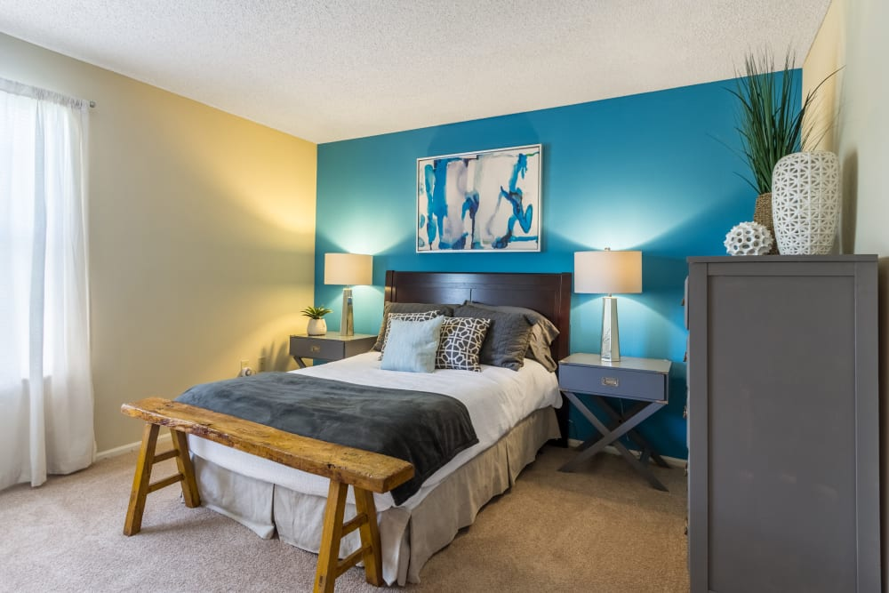 Bedroom with blue painted accent wall and bench at the foot of bed In an apartment at Britton Woods in Dublin, Ohio
