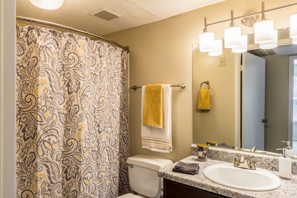 Bathroom featuring large vanity mirror and shower bathtub in an apartment at Britton Woods in Dublin, Ohio