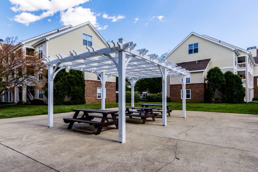 Picnic table seating with shade structure and apartments in the background at Britton Woods in Dublin, Ohio
