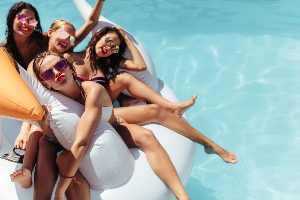 Friends sharing a pool floaty at UNCOMMON Wilmington in Wilmington, North Carolina