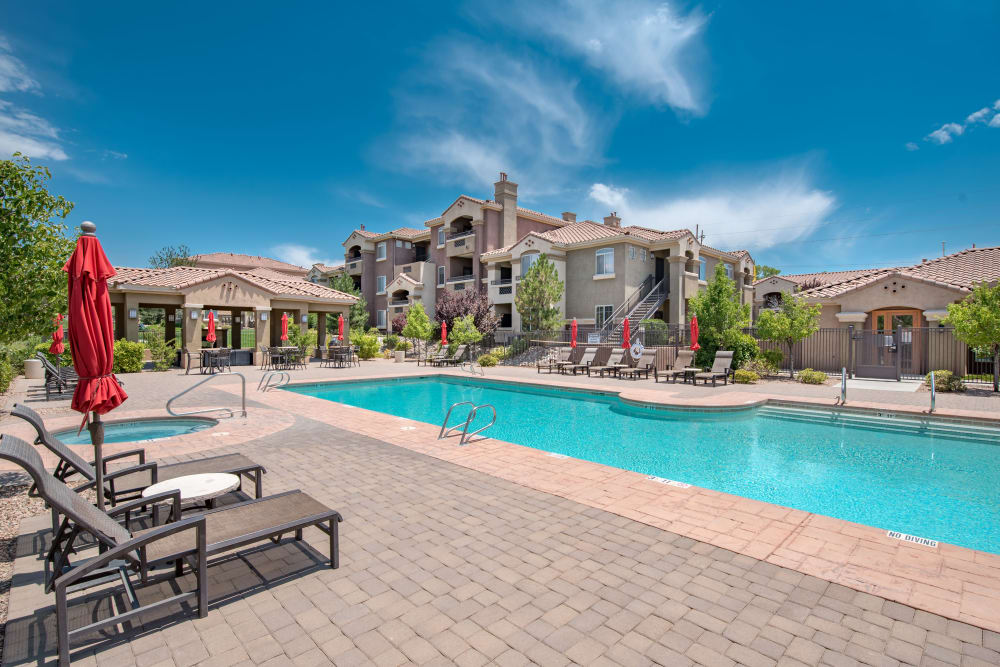 Community pool with lounge chairs and mature trees in the distance at Broadstone Towne Center in Albuquerque, New Mexico