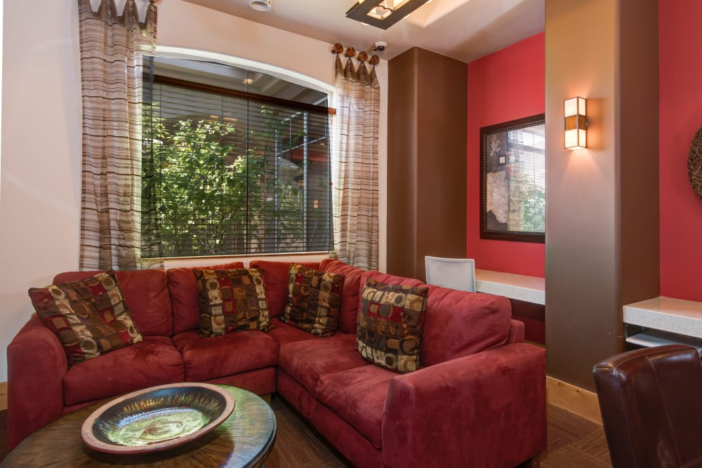 Well decorated clubhouse interior features large burgundy colored sectional couch and art on the walls at Broadstone Towne Center in Albuquerque, New Mexico