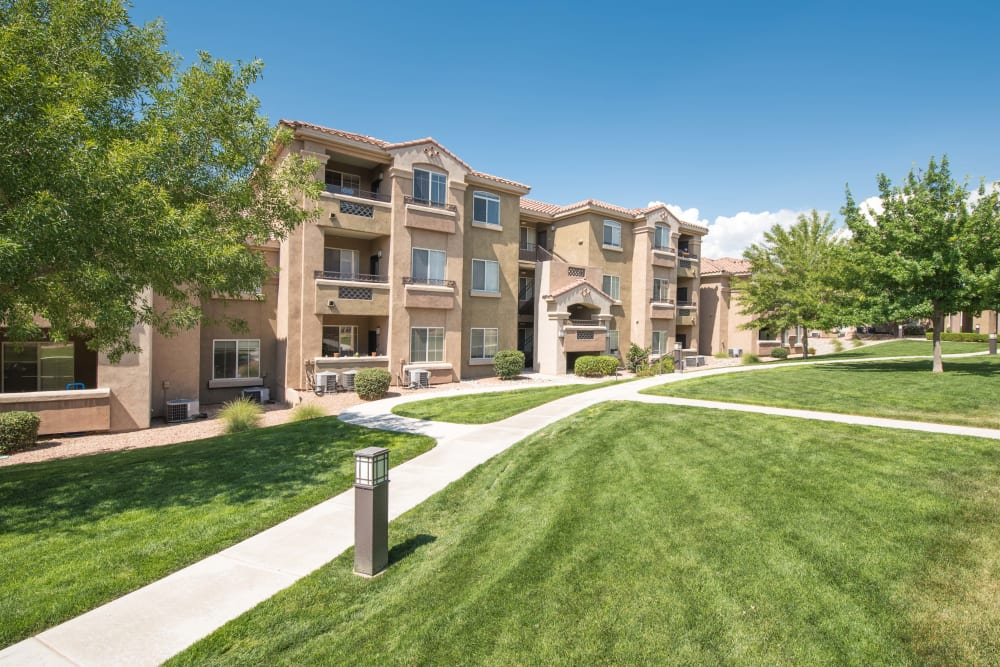 Exterior of apartment buildings and well manicured lawn with walkways at Broadstone Towne Center in Albuquerque, New Mexico