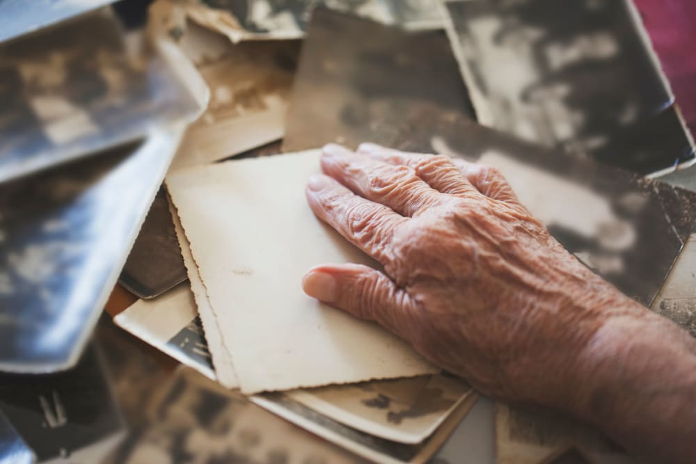 A resident's hand and collection of old photographs at Westminster Memory Care in Aiken, South Carolina