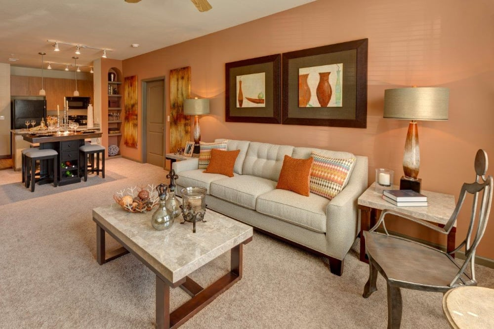 Large living room with plush carpeting and a ceiling fan at The Addison at South Tryon in Charlotte, North Carolina