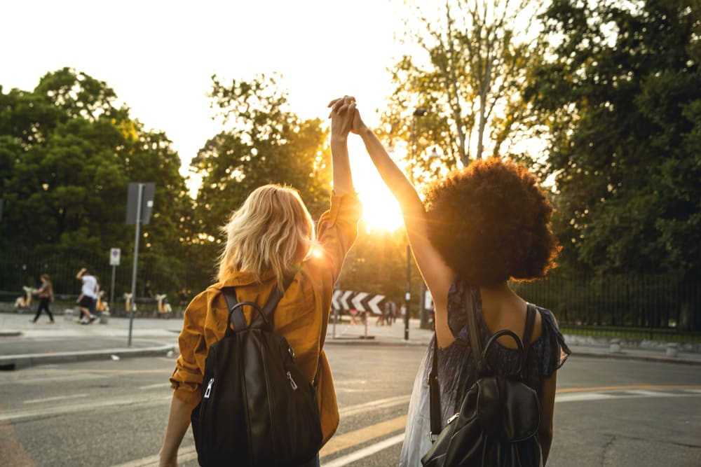 Friends holding hands while looking at the sunset at evolve Bloomington in Bloomington, Indiana