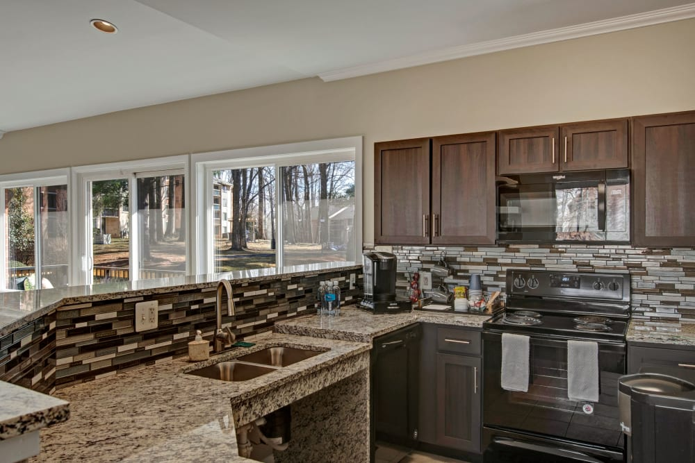 Large clubhouse kitchen with the tile backsplash and granite countertops at West Springfield Terrace in Springfield, Virginia