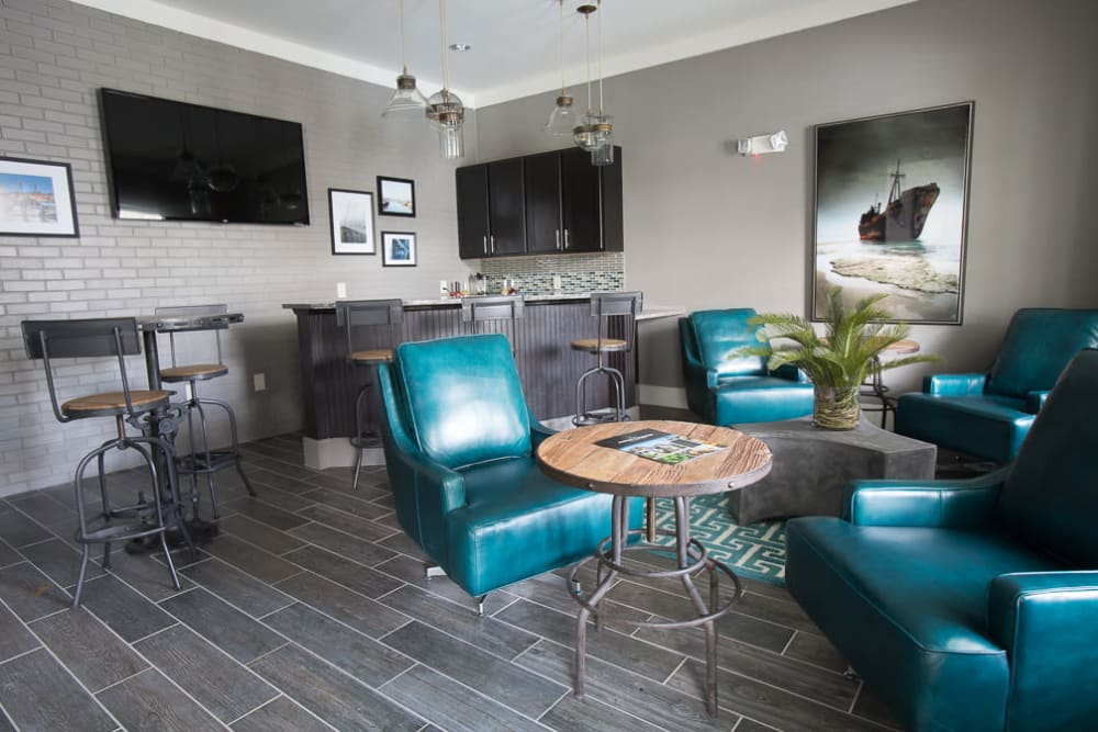 Clubhouse lounge with bar seating and flat-screen TVs at Ansley Commons Apartment Homes in Ladson, South Carolina