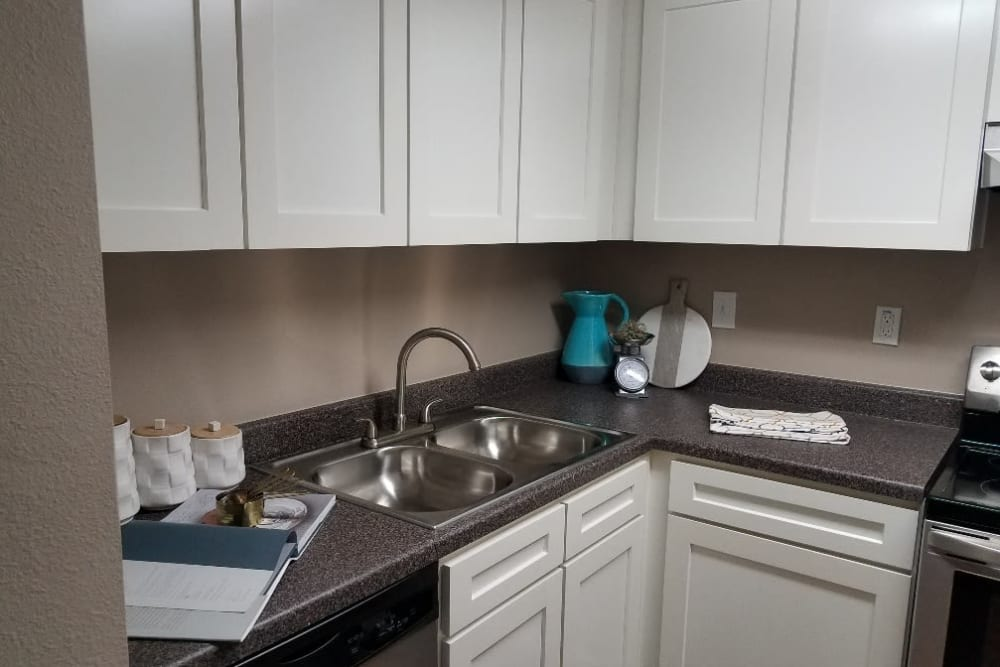 Kitchen with granite countertops and white wood cabinets at The Villages at Meyerland in Houston, Texas