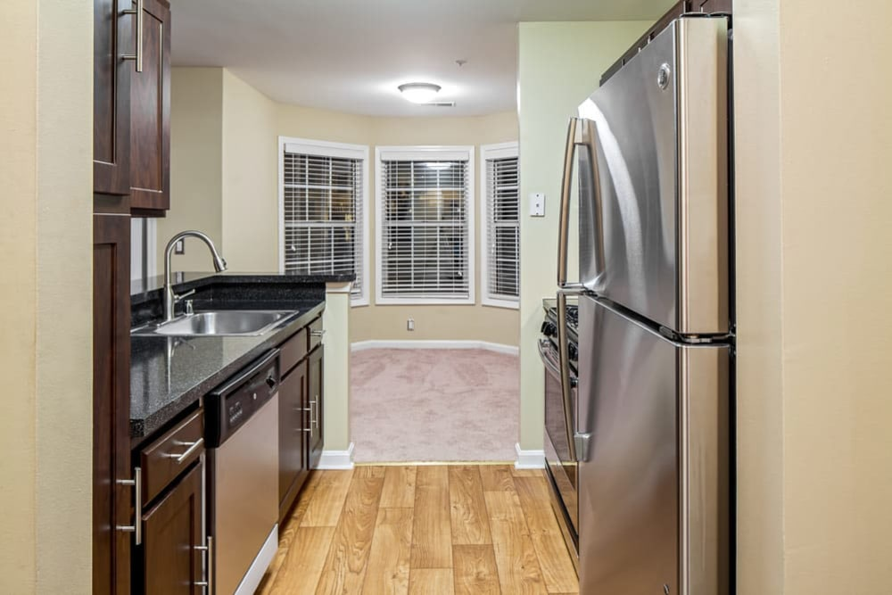 Modern kitchen with stainless steel appliances and granite countertops at Sussex at Kingstowne in Alexandria, Virginia