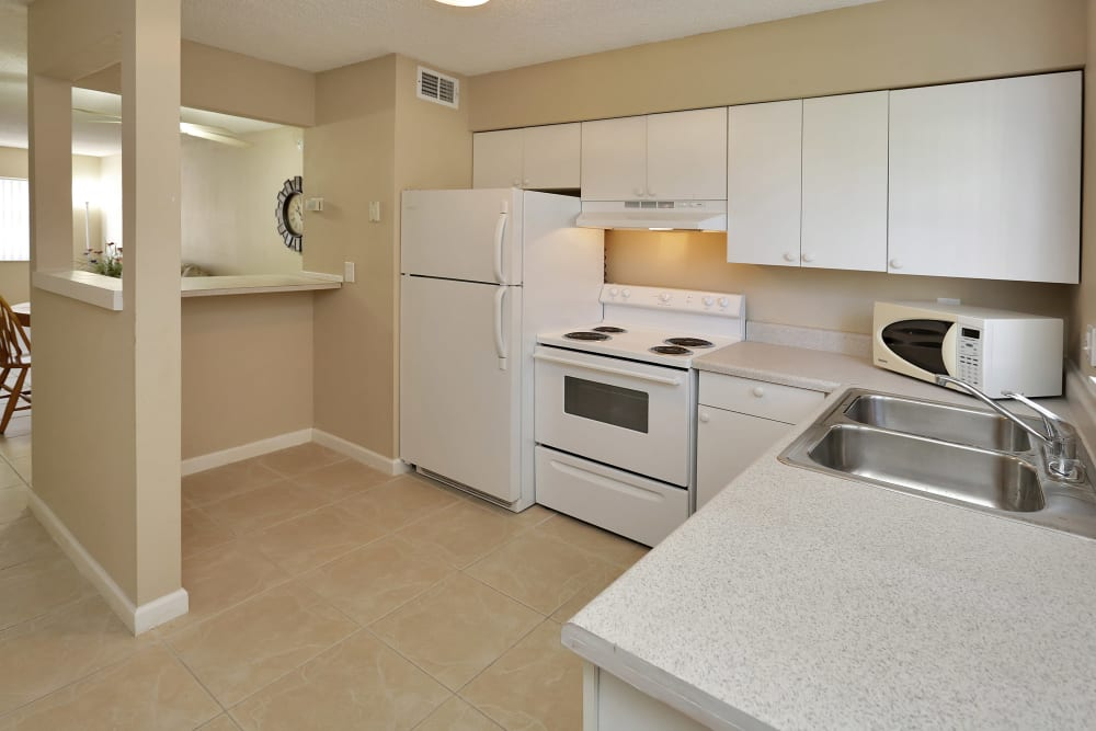 Modern kitchen with white wood cabinets and bar at Stonewood Townhomes in Melbourne, Florida