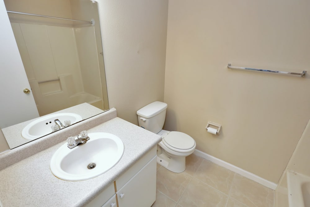 Model bathroom with large vanity mirror at Stonewood Townhomes in Melbourne, Florida