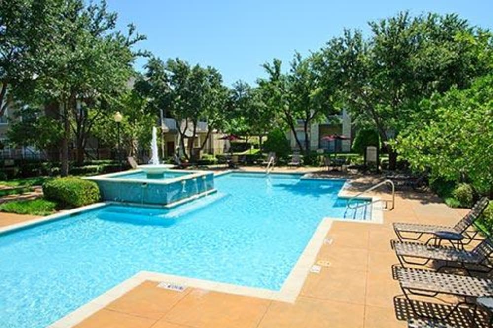 Resort style pool with lounge chairs at Somerset at Spring Creek in Plano, Texas