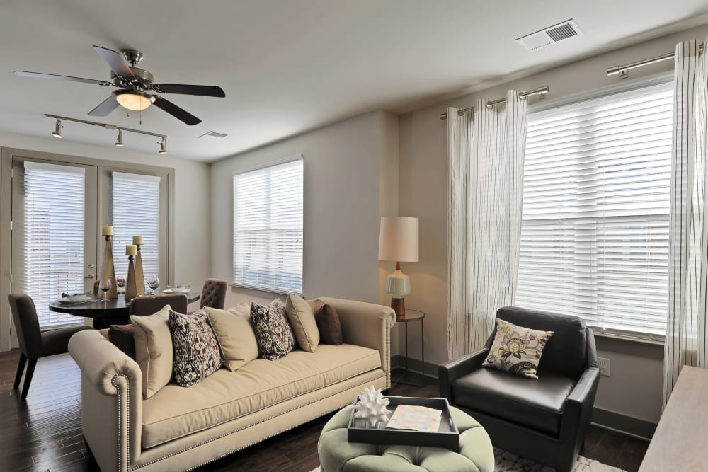 Living room with a ceiling fan and hardwood floors in the model home at The Mark at Brickyard Apartment Homes in Beltsville, Maryland