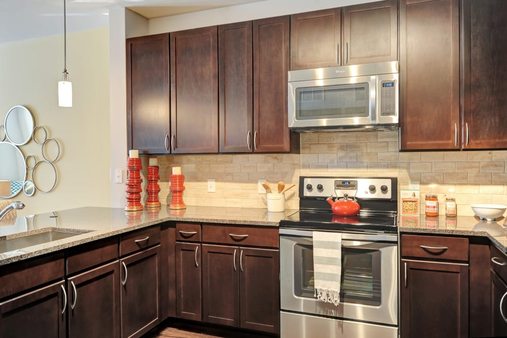 Granite countertops and stainless steel appliances In the kitchen at The Mark at Brickyard Apartment Homes in Beltsville, Maryland