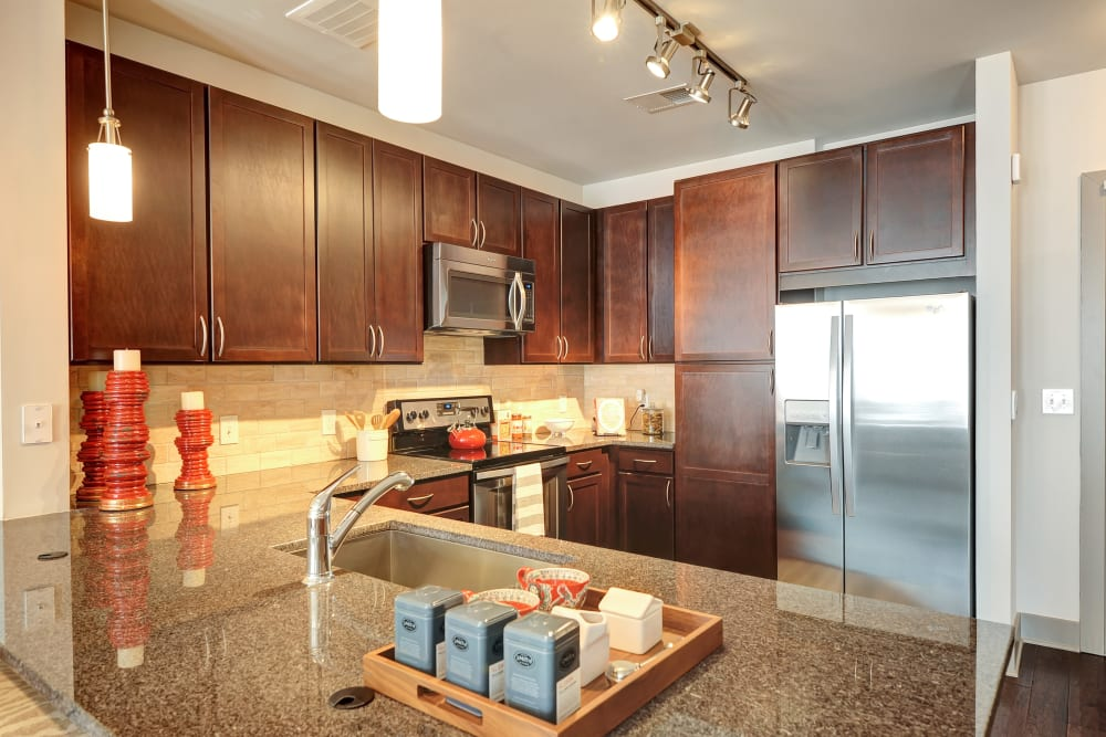 Model kitchen with granite countertops and dark wood cabinets at The Mark at Brickyard Apartment Homes in Beltsville, Maryland