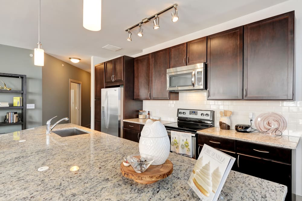 Granite countertop kitchen and island in the model unit at The Mark at Brickyard Apartment Homes in Beltsville, Maryland