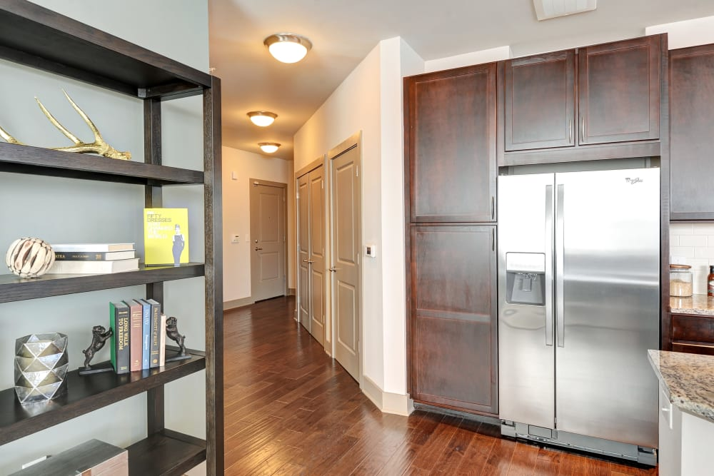 View of hallway and hardwood floors in the kitchen at The Mark at Brickyard Apartment Homes in Beltsville, Maryland