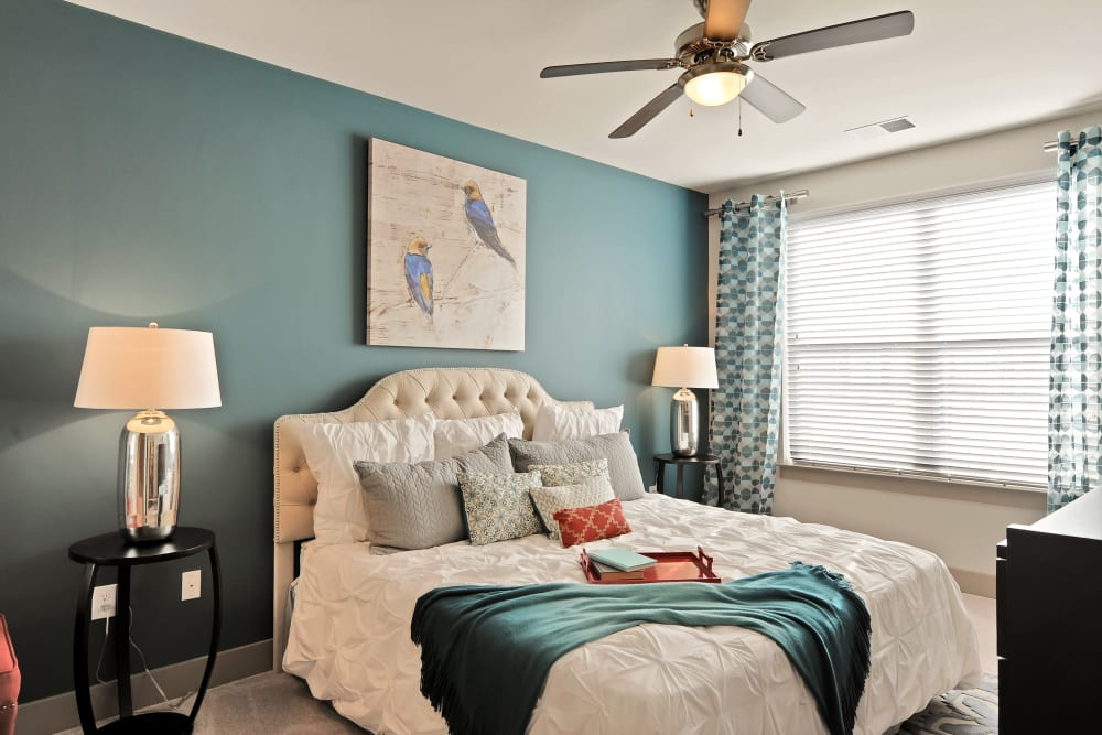 Model bedroom with a ceiling fan and Blue painted walls at The Mark at Brickyard Apartment Homes in Beltsville, Maryland
