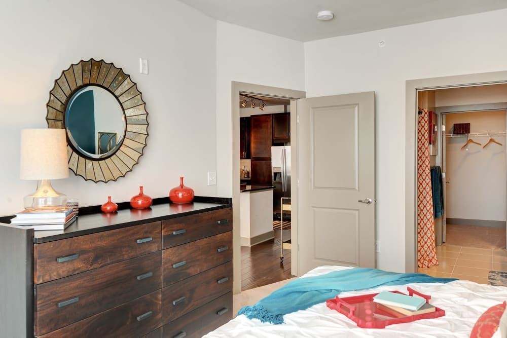Model bedroom with dark wood dresser and walk-in closet at The Mark at Brickyard Apartment Homes in Beltsville, Maryland