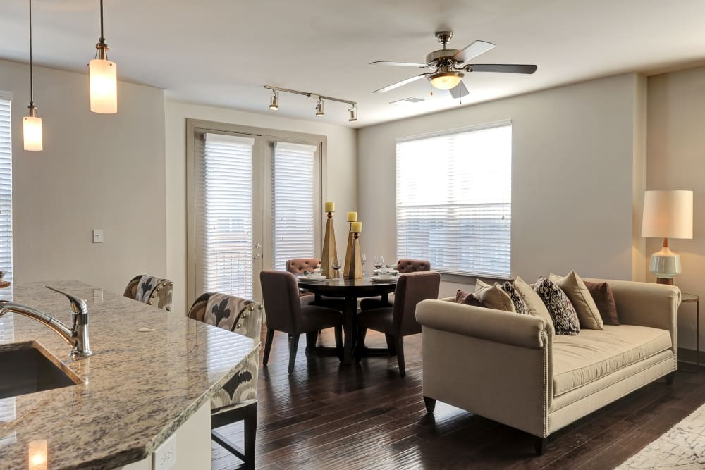 Well lit living room with modern decor in the model home at The Mark at Brickyard Apartment Homes in Beltsville, Maryland