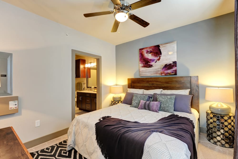 Well lit model bedroom with ceiling fan at The Mark at Brickyard Apartment Homes in Beltsville, Maryland