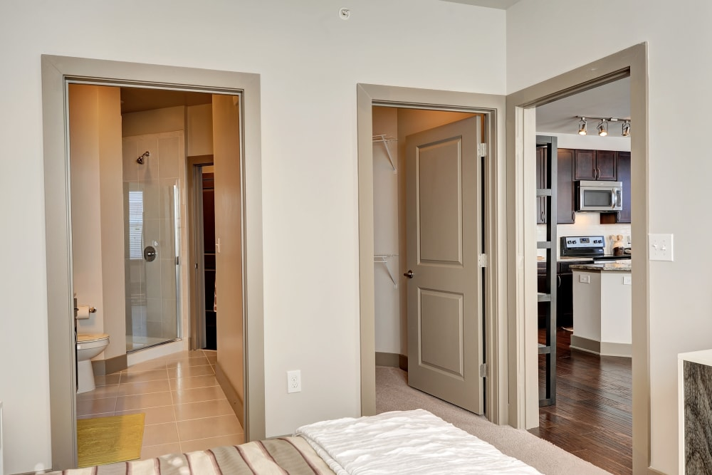 Model bedroom with a view of the attached walk-in closet and bathroom at The Mark at Brickyard Apartment Homes in Beltsville, Maryland