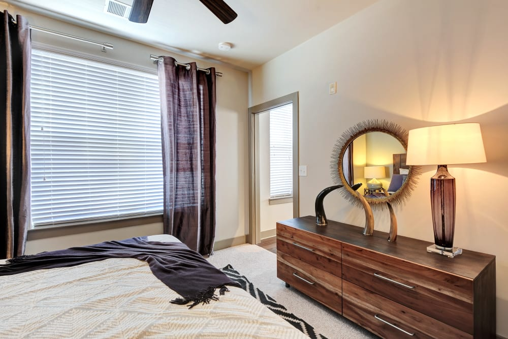 Model bedroom with dark wood dresser and ceiling fan at The Mark at Brickyard Apartment Homes in Beltsville, Maryland