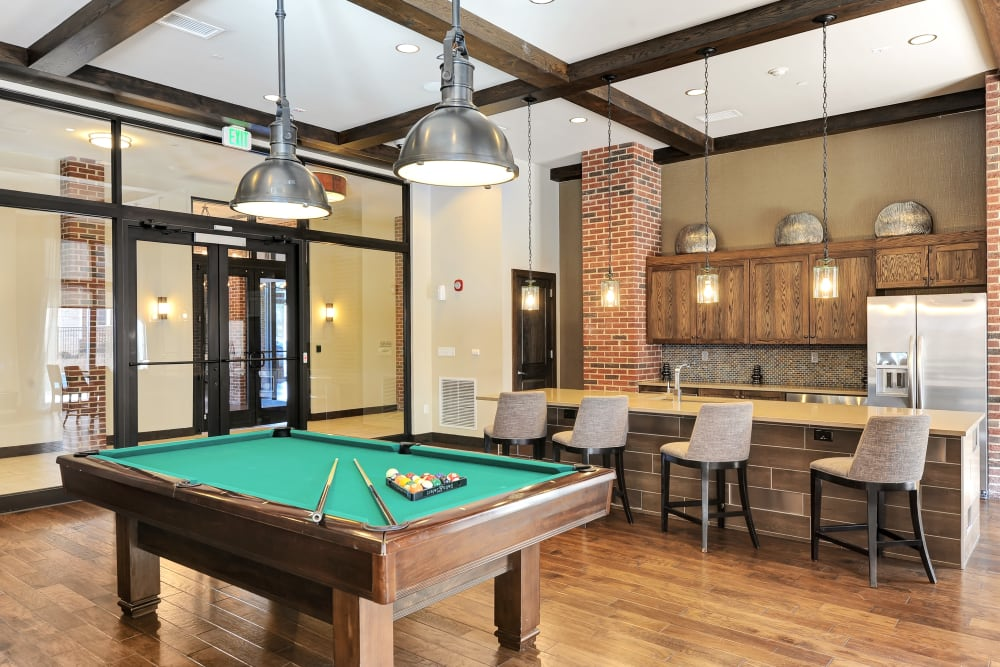 Pool table and kitchen available in the clubhouse at The Mark at Brickyard Apartment Homes in Beltsville, Maryland
