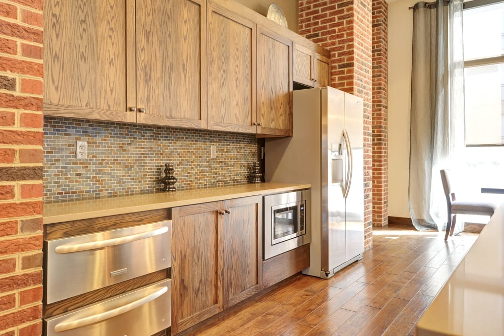 Brick walls and stainless steel appliances in the Clubhouse kitchen at The Mark at Brickyard Apartment Homes in Beltsville, Maryland