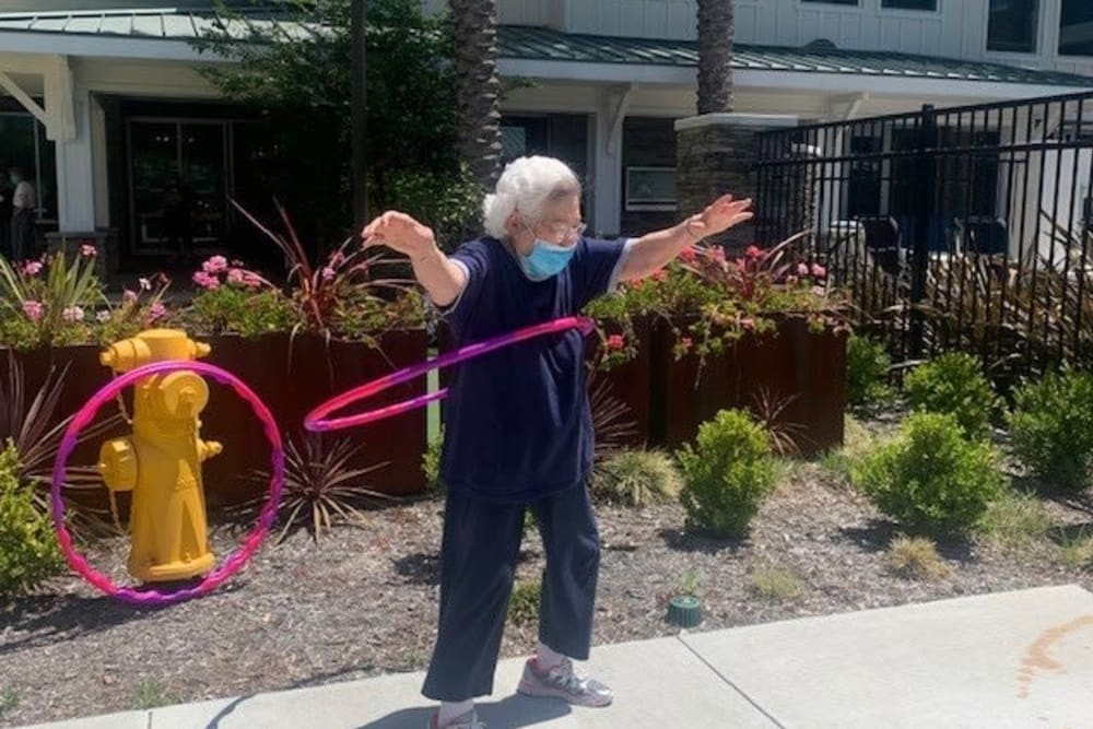 Residnet hula-hooping outside in a mask at Clearwater Living