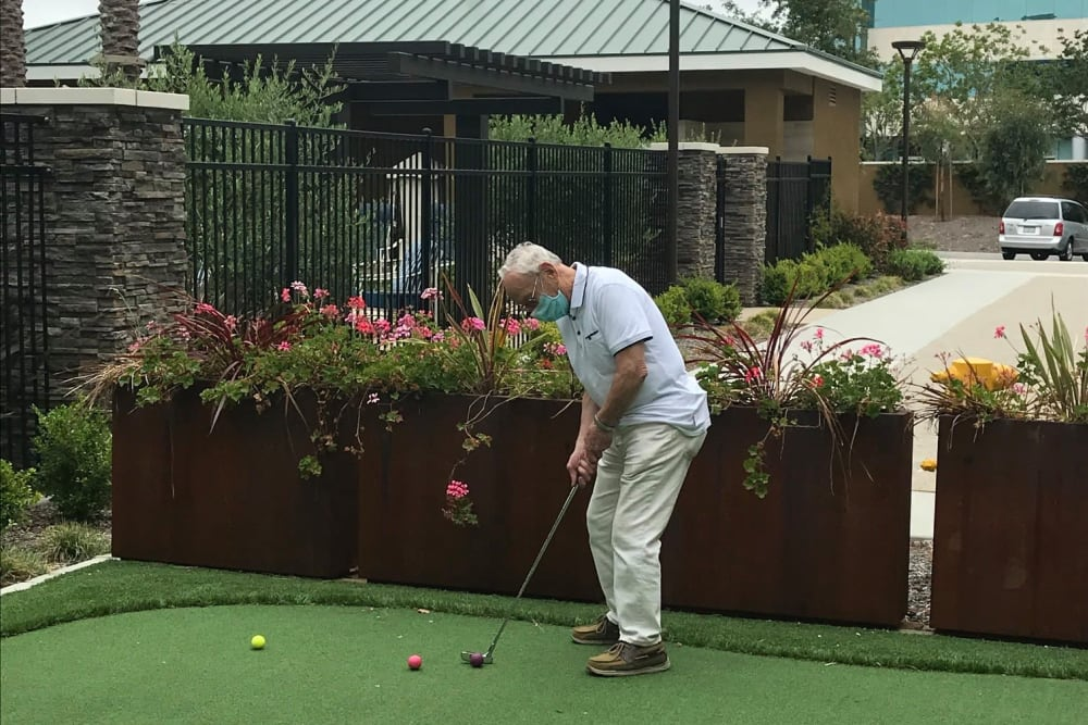 Resident playing mini-golf in a mask at Clearwater at Riverpark