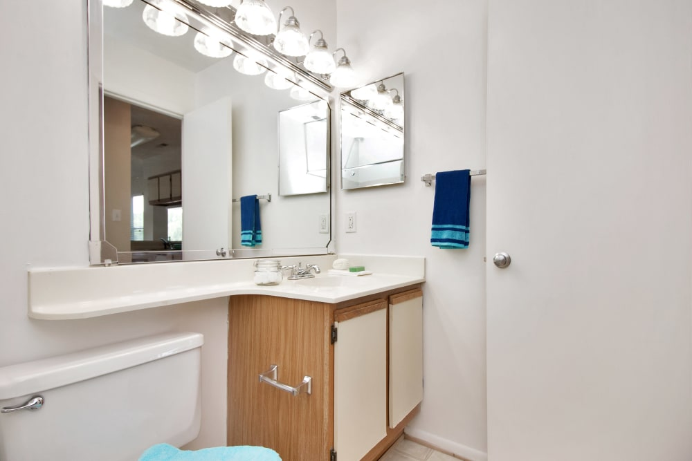 Model bathroom with large vanity mirror at Runaway Bay Apartments in Virginia Beach, Virginia