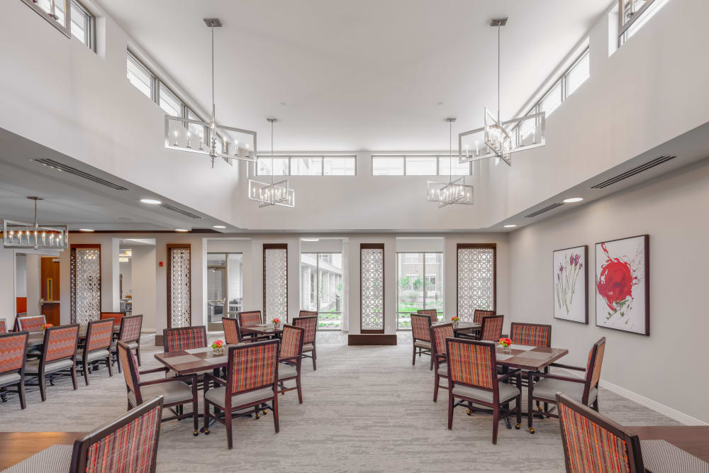 Evenly lit dining area with several spaced out dining tables at Aspired Living of La Grange in La Grange, Illinois